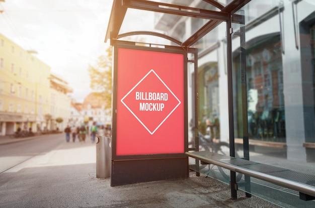Mockup del tabellone per le affissioni della fermata dell'autobus. luce del sole e strada
