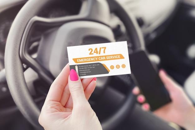Biglietto da visita nella mano di una ragazza seduta in un modello di auto