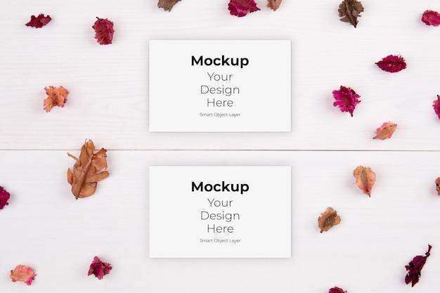 Mockup di biglietto da visita e fiore secco sulla tavola di legno