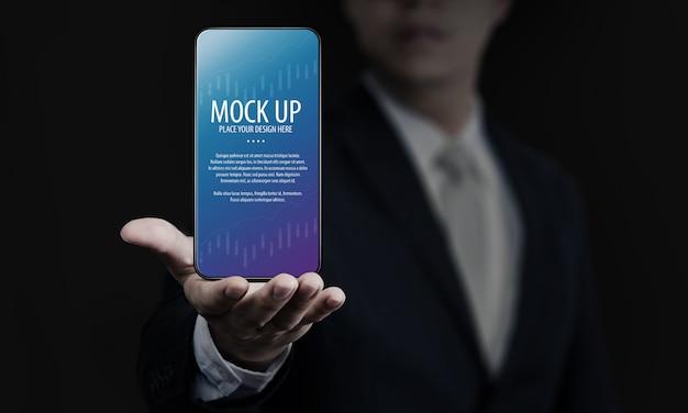 Modello dello schermo dello smartphone della tenuta dell'uomo di affari