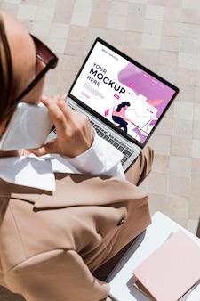 Donna di affari che tiene il suo modello di laptop