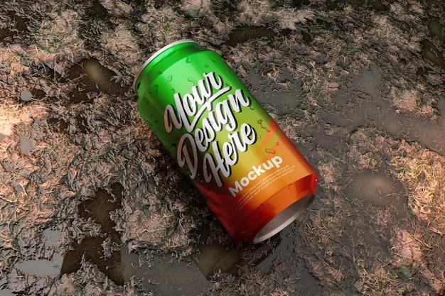Mockup di bevande in scatola sulla superficie del terreno bagnato