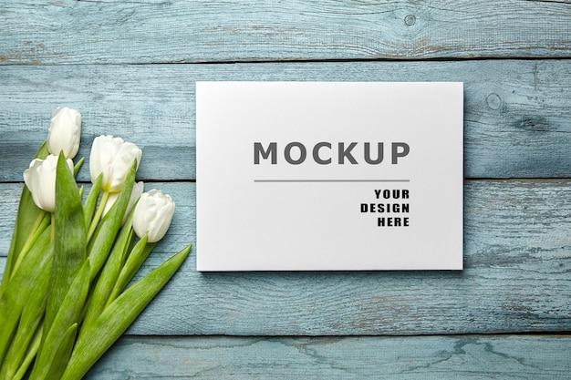 Mockup di stampa su tela e fiori di tulipano bianco su superficie di legno blu chiaro