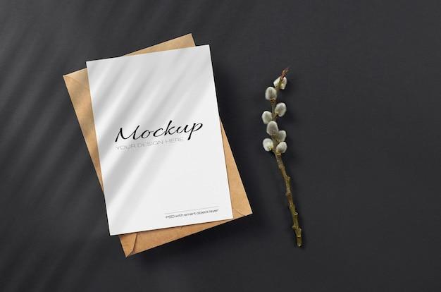 Mockup di carta con busta su carta di colore nero con ramoscello di salice primaverile e ombra