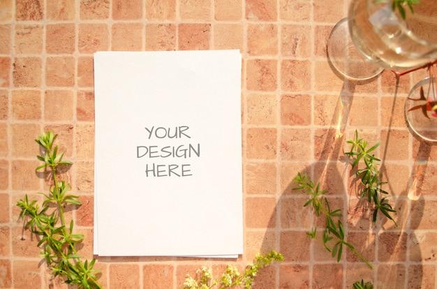Mockup di carta con erbe, bicchieri di vino e ombre che cadono su uno sfondo di colore pesca.