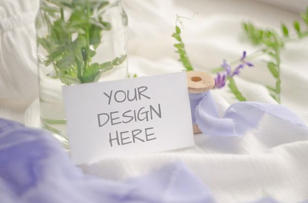 Mockup di carta con fiori viola e delicati nastri di seta su uno sfondo bianco