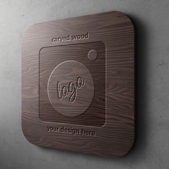 Scolpito su modello di mockup logo in legno scuro su rettangolo arrotondato con muro di cemento