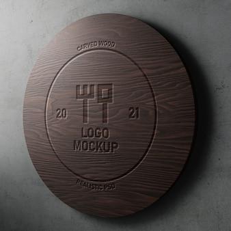 Mockup logo realistico effetto inciso intagliato su legno rotondo moderno su muro di cemento