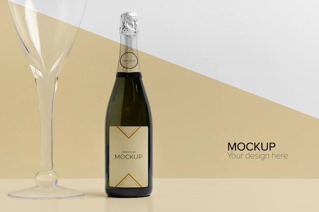 Mock-up di bottiglia di champagne e bicchiere di champagne