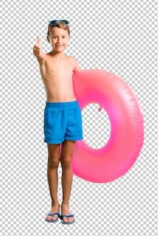 Bambino in vacanza estiva dando un pollice in alto gesto e sorridente