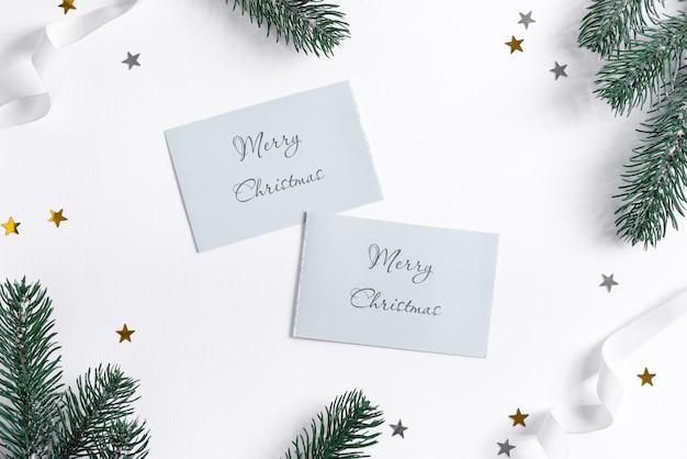 Cartolina di natale con ramoscelli di abete, coriandoli e carte mockup