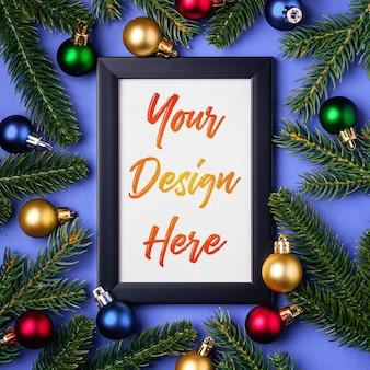 Composizione in natale con cornice vuota con ornamenti colorati e rami di abete