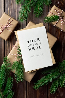 Mockup di biglietto di auguri di natale con scatole regalo di natale e rami di abete
