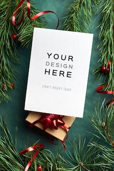 Mockup di biglietto di auguri di natale con scatola regalo decorata e rami di pino sul verde