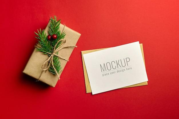 Mockup di biglietto di auguri di natale con confezione regalo decorata