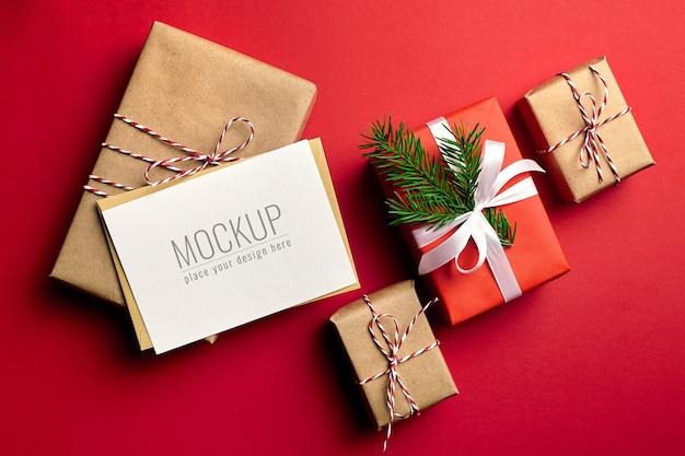 Mockup di biglietto di auguri di natale con scatole regalo decorate su colore rosso