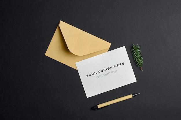 Mockup di biglietto di auguri di natale con busta e ramoscello di abete su sfondo di carta scura