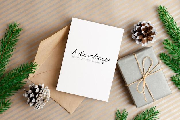 Modello di biglietto di auguri di natale con busta, confezione regalo e rami di abete e decorazioni di coni