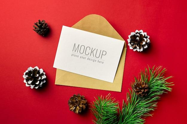 Mockup di biglietto di auguri di natale con busta e rami di pino con coni su rosso