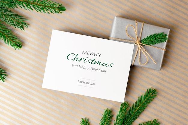 Modello di biglietto di auguri di natale con confezione regalo e rami di abete verde