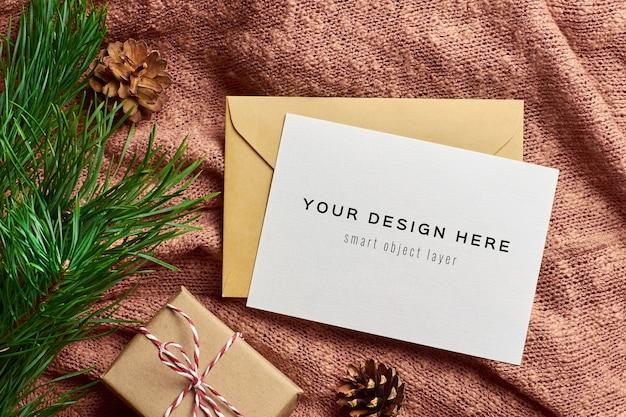 Mockup di biglietto di auguri di natale con scatola regalo e ramo di un albero di pino