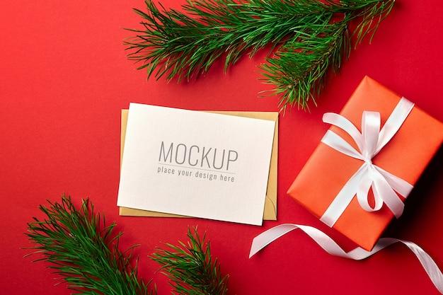 Mockup di biglietto di auguri di natale con scatola regalo e rami di pino sul rosso