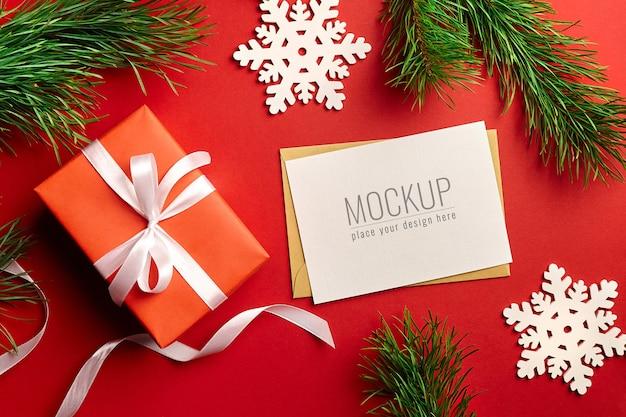 Mockup di biglietto di auguri di natale con scatola regalo, rami di pino e decorazioni in legno