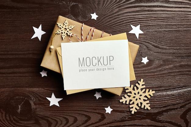 Mockup di biglietto di auguri di natale con scatola regalo e decorazioni in legno