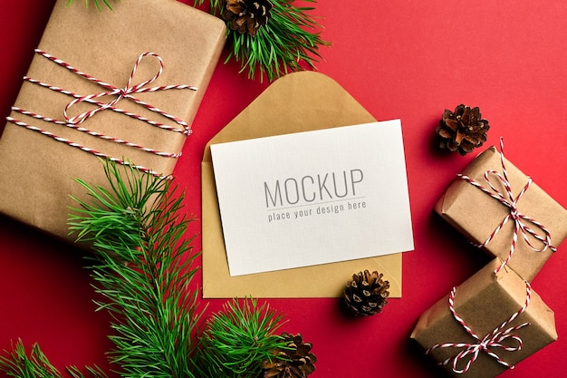 Mockup di biglietto di auguri di natale con scatole regalo e rami di pino e coni sul rosso