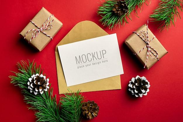 Mockup di biglietto di auguri di natale con scatole regalo e rami di pino con coni sul rosso