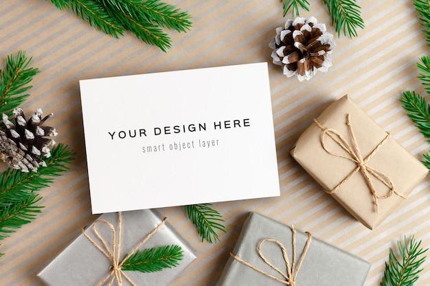 Modello di biglietto di auguri di natale con scatole regalo e decorazioni di pigne di pino