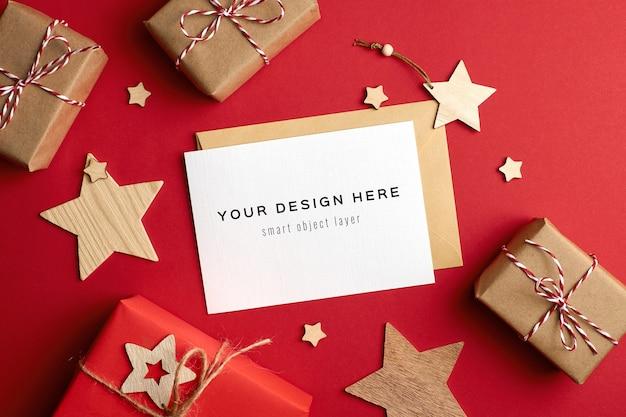 Mockup di biglietto di auguri di natale con scatole regalo e decorazioni in legno sul rosso