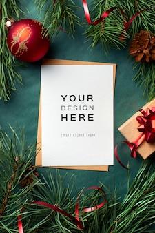 Mockup di biglietto di auguri di natale con rami di pino e decorazioni festive