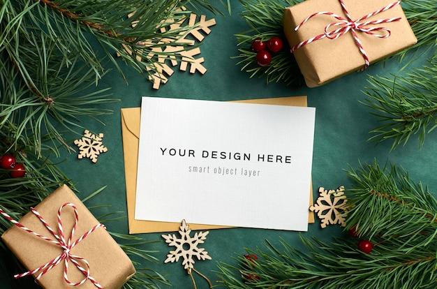Mockup di biglietto di auguri di natale con rami di pino e scatole regalo con decorazioni in legno su verde