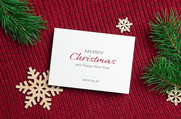 Modello di biglietto di auguri di natale con decorazioni di fiocchi di neve in legno e rami di pino su fondo a maglia