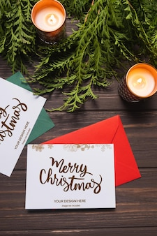 Lettere di natale e biglietti di auguri giacciono su un tavolo di legno marrone con rami di abete e candele mockup
