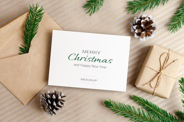 Modello di biglietto di auguri di natale o capodanno con busta, confezione regalo e decorazioni di pigne