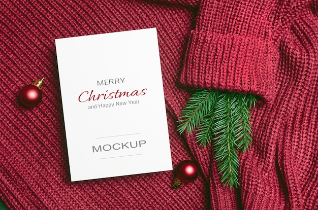 Modello di biglietto di auguri di natale o capodanno con decorazioni di palline rosse e ramo di abete su sfondo a maglia