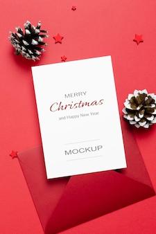 Modello di biglietto di auguri o invito di natale o capodanno con decorazioni di buste e coni su rosso