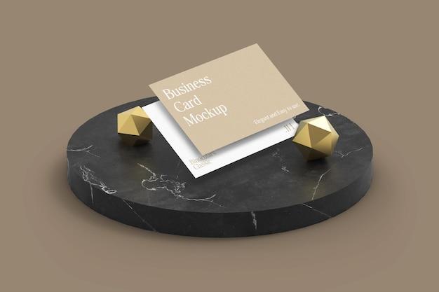 Mockup di biglietti da visita classici ed eleganti con sovrapposizione di ombre su pietra di marmo con oggetti dorati