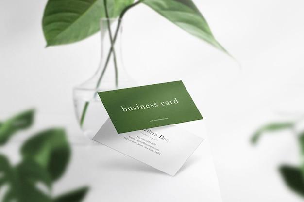 Pulisci il modello minimo di biglietto da visita che galleggia sul tavolo bianco superiore con vaso e foglie