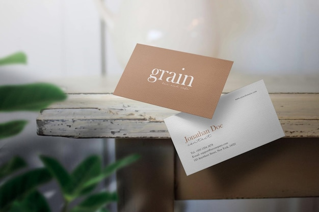 Pulisci il lato del tavolo mockup biglietto da visita minimo con foglie verdi