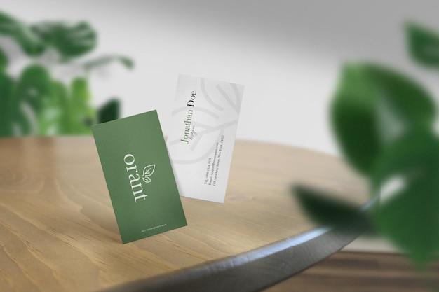 Pulisci il mockup minimo del biglietto da visita sul tavolo superiore con sfondo di foglie. file psd.