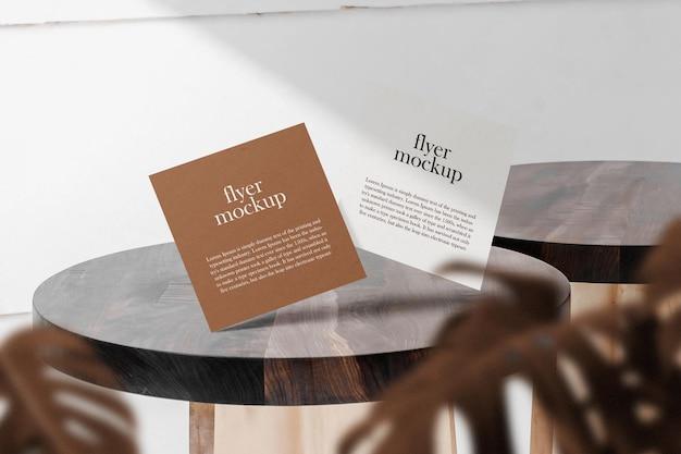 Pulisci il modello di volantino quadrato minimale che galleggia sul tavolo superiore con foglie.