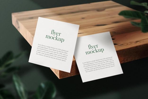 Pulisci il modello di volantino quadrato minimo che galleggia sul piatto di legno con foglie