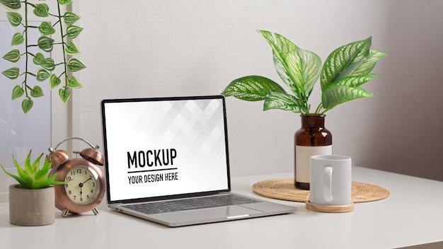Primo piano sull'area di lavoro biophilia con mockup di laptop e vaso di piante nella stanza dell'home office
