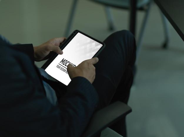 Chiuda in su dell'uomo d'affari utilizzando il modello di tavoletta digitale