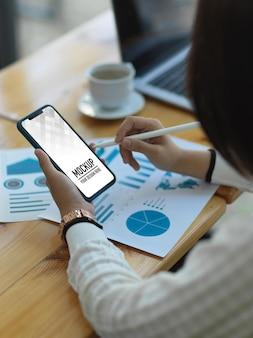 Close up imprenditrice utilizza lo smartphone durante l'analisi del grafico aziendale nella stanza dell'ufficio
