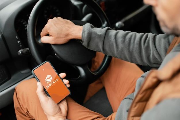 Chiuda sull'uomo di consegna che tiene smartphone