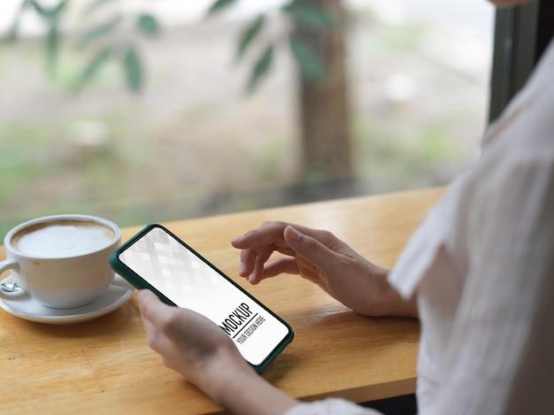 Chiuda in su della femmina utilizzando il mockup dello smartphone